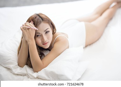 Young asian woman in fashion white one piece posing in her bed