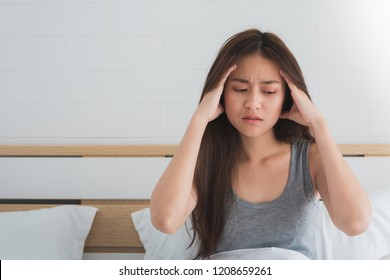 Young Asian woman feel headaches and discomfort on bed in white bedroom morning.Concept of women's health care.