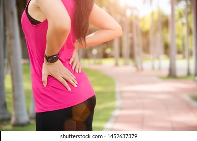 Young asian woman feel pain on her back and hip while exercising, healthcare concept.