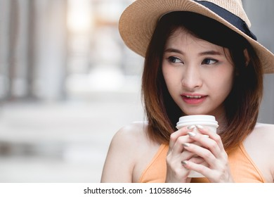 Young Asian woman feeling happy holding coffee cup looking away.