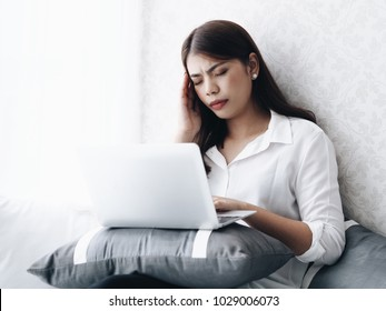 Young Asian woman feeling unwell during working with tablet in office.