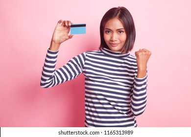 Young Asian woman fist pump with blank card on pink background