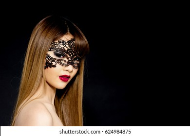 Young Asian woman flirting isolated on black background. Portrait of beautiful Asian woman with erotic black lace mask and subtle smile expression gestures for desire, flirting, fantasy concepts.
