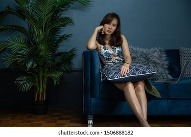 Young asian woman freelancer look at the camera and sit on modern sofa near the laptop with green palm tree in living room at home. Work at home concept.