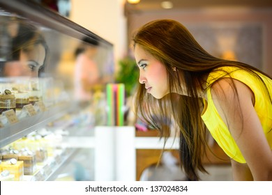 young Asian woman in front of sweet candy food store window