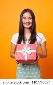 Young Asian woman with a gift box on bright yellow background
