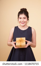 Young Asian woman with a gift box  on beige background