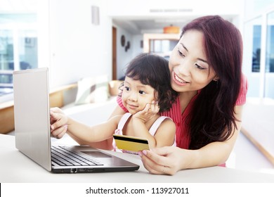 Young asian woman gives online shopping education to her daughter, shot at home