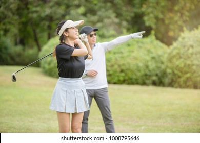 Young Asian woman golfer doing practice with her professional golf trainer at the golf club