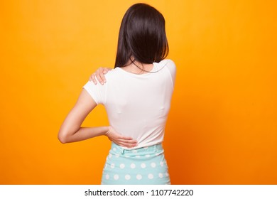 Young Asian woman got back pain on bright yellow background