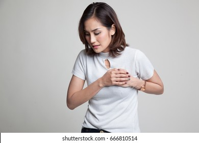 Young Asian woman got chest pain on gray background