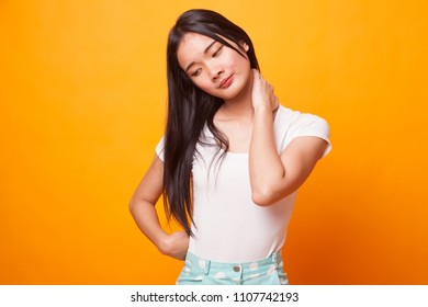 Young Asian woman got neck pain on bright yellow background