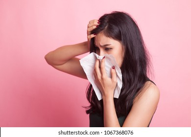 Young Asian woman got sick and flu on pink background