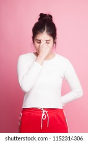 Young Asian woman got sick and  headache on pink background