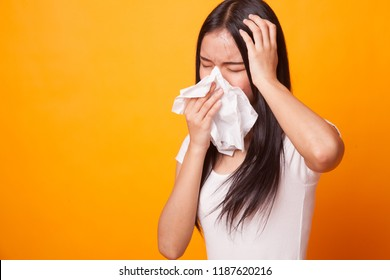 Young Asian woman got sick and flu on bright yellow background