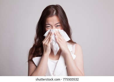 Young Asian woman got sick and flu on gray background