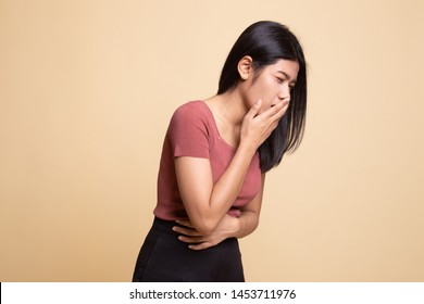 Young Asian woman got stomachache about to vomit on beige background