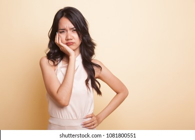 Young Asian woman got toothache  on beige background