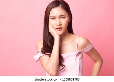 Young Asian woman got toothache on pink background