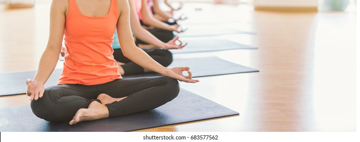 young Asian woman group exercising and sitting in yoga lotus position in yoga classes