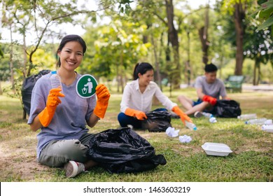 Young Asian woman and group of volunteers collecting garbage waste into trash bin bag and holding a plastic bottle in the park. Save the earth and environmental concern concept