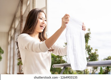 young asian woman hanging the laundly