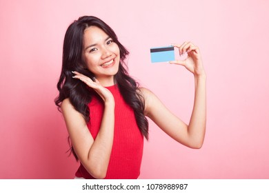 Young Asian woman happy with  blank card on pink background