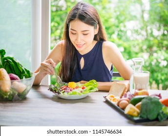 Young asian woman happy eating healthy salad sitting on the table indoors. Green healthy food concept.