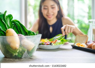 Young Asian Woman Happy Enjoying While cooking healthy food In Kitchen. Detox Diet, Weight Loss Nutrition Concept