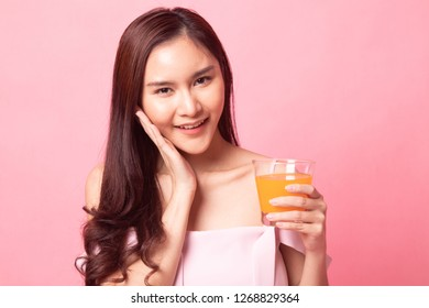 Young Asian woman happy smile with orange juice on pink background