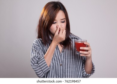 Young Asian woman hate tomato juice on gray background
