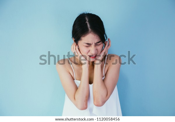 Young Asian woman having earache or ear pain isolated over blue background