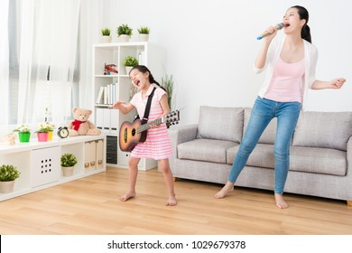 Young Asian woman and her daughter enjoying singing and playing music in the living room.