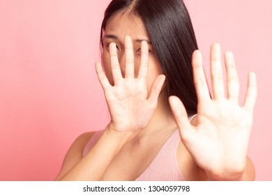 Young Asian woman hide her  face on pink background