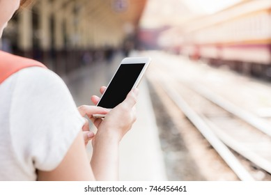 Young Asian Woman hold and looking at her mobile phone in the train station