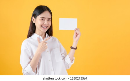 Young Asian woman holding blank paper with smiling face and looking on the yellow background. for advertising signs.