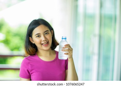 Young asian woman holding a bottle of cold water