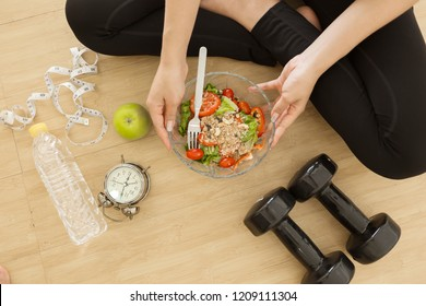 Young asian woman holding bowl of salad  with dumbell at home. Fitness and healthy lifestyle concept