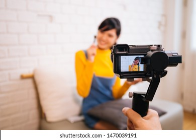 Young Asian woman holding cosmetics brush while recording a video with professional camera. Beauty vlog blogging and internet influencer business concept