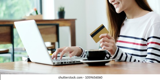 Young asian woman holding credit card and using laptop computer for shopping on line at cafe, business and technology concept, digital marketing, casual lifestyle