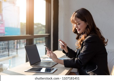 Young asian woman holding credit card and using mobile phone. Online shopping concept