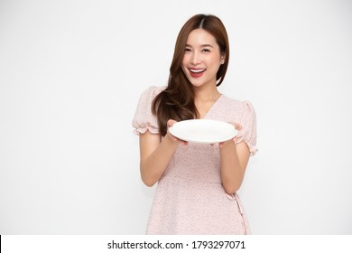 Young Asian woman holding empty white plate or dish isolated on white background