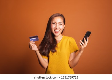 Young Asian woman holding fake credit card and smart phone for online shopping, payment over orange background