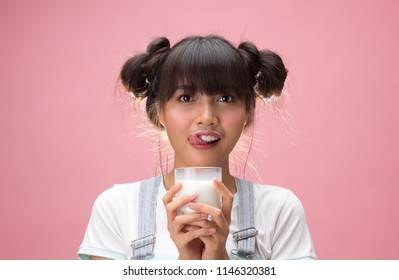 Young asian woman holding a glass of milk with happiness