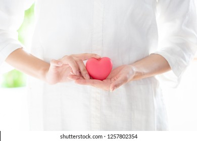 young asian woman holding heart symbol