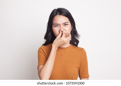 Young Asian woman  holding her nose because of a bad smell on white background