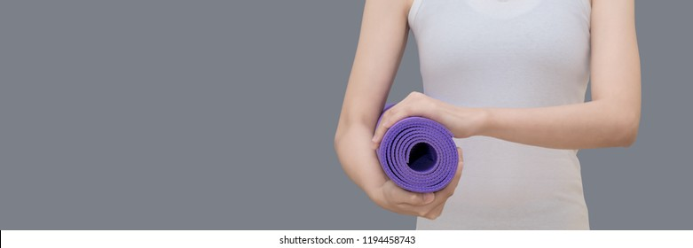 Young asian woman holding her yoga mat while go to practice yoga exercise at the yoga sport gym.Photo design in banner cover size with copy space for add text.