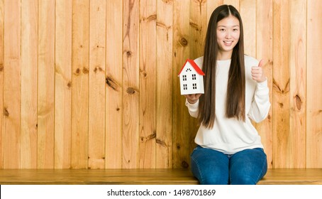 Young asian woman holding a house icon smiling and raising thumb up