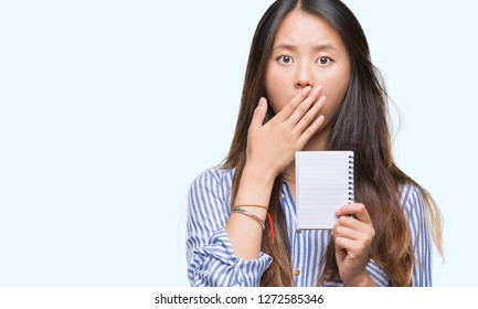Young asian woman holding notebook over isolated background cover mouth with hand shocked with shame for mistake, expression of fear, scared in silence, secret concept