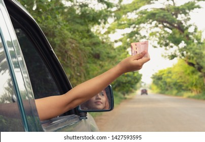 Young Asian woman holding out paper money through a car window to pay a toll fee - Tanned millennial female holding Thai currency banknote from a vehicle to pay a corruption bribe